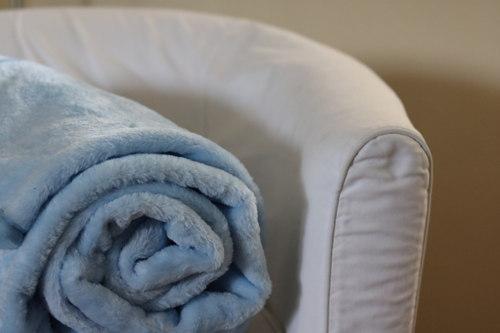 Manta azul sobre sofá beige. Ideasdecasa