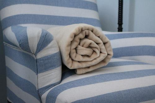 Manta beige sobre sofa azul y blanco. Ideasdecasa